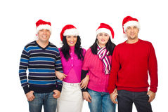 United friends with Santa hats. United friends standing in a row and wearing Santa hats isolated on white background Stock Photography