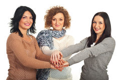 United friends women. Standing with their hands on top each other isolated on white background Stock Images