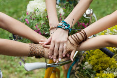 United hands of girlfriends closeup, young girls in boho bracelets. United hands of young females. Stylish girlfriends in boho hippie bracelets near bicycle royalty free stock images