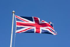 United Kingdom flag. Waving against blue sky from an old flagpole stock photos