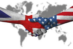 United Kingdom flag and USA flag across handshake. Stock Photos