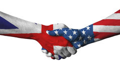 United Kingdom flag and USA flag across handshake. Royalty Free Stock Photos