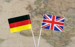 The United Kingdom and Germany flag pins on a world map background, political relations concept. Paper flag pins of Germany and the United Kingdom on a world map stock photos