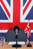 United Kingdom news desk. Photo of a United Kingdom themed conference desk with microphone and flags Stock Photo