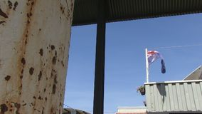 United Kingdom`s flag on top of a warehouse. A worms eye view shot of united kingdom`s flag on top of a warehouse stock footage