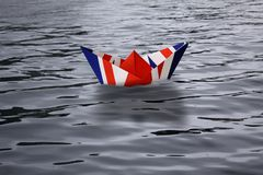 United Kingdom sailing alone in the sea like a paper ship made as the English flag Union Jack - Brexit concept showing England lea royalty free stock image