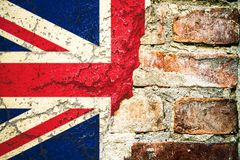 Brexit: United Kingdom UK flag flag painted cracked divided peeling paint brick wall cement facade Brexit concept. royalty free stock image