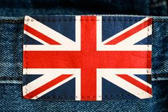 United Kingdom UK national flag on jeans leather label tag blue red white colours over denim background.  royalty free stock photo