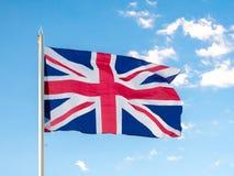 United Kingdom union jack flag. Union Jack, traditional United Kingdom flag, waving in blue sky, copyright space Stock Images
