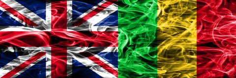 United Kingdom vs Mali smoke flags placed side by side. Thick colored silky smoke flags of Great Britain and Mali.  Stock Images