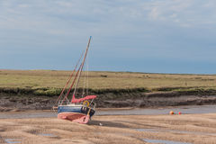 United Kingdom - Wells Next The Sea. Pleasure boat during low tide against a cloudy sky in the village of Wells Next The Sea, Norfolk Stock Image