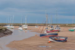 United Kingdom - Wells Next The Sea. Pleasure boats during low tide against a cloudy sky in the village of Wells Next The Sea, Norfolk Stock Images