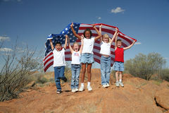 United Nation. A diverse group of children enveloped under the American flag outdoors symbolizing our diverse country stock photo
