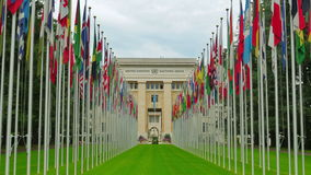 United Nations building with flags, Geneva, Switzerland, zoom in, 4K stock video footage