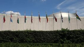 United Nations General Assembly. The United Nations General Assembly building, in New York City. The flags of its member countries are outside, in alphabetical stock footage