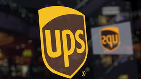 United Parcel Service UPS logo on the glass against blurred business center. Editorial 3D rendering Stock Photos