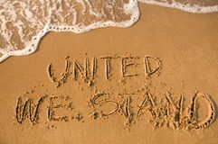 United we stand. Sign written on a beach, water approaching Royalty Free Stock Images