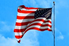 United Stated US American patriotic flag red blue color sky. United Stated US American patriotic flag red blue white color sky and clouds background Stock Photography