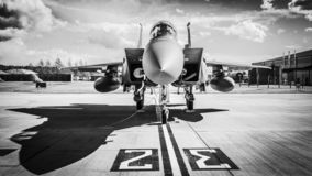 Fighter jet on runway. United States Air Force F15 Strike Eagle fighter jet on the runway of military airbase. Black and white.   front intake intakes shadow stock image