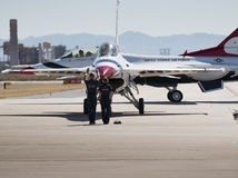 United States Air Force Thunderbirds. A flight crew directs an Thunderbirds F-16 fighter jet on the runway. The United States Air Force Thundbirds Air royalty free stock photo