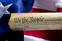 United States of America Constitution Scroll. A copy of the United States of America Constitution scroll in front of a large American Flag, focus is on the word Stock Photo