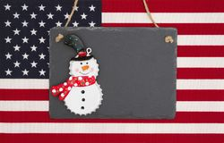 United States of America flag with a black chalkboard with snowm Royalty Free Stock Photo