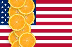United States of America flag and citrus fruit slices vertical row. United States of America flag and vertical row of orange citrus fruit slices. Concept of royalty free stock photo