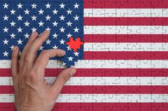 United States of America flag is depicted on a puzzle, which the man`s hand completes to fold.  stock image