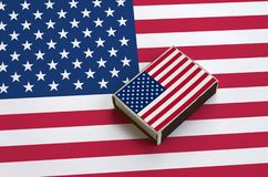 United States of America flag is pictured on a matchbox that lies on a large flag.  stock images