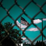 A flag waving in the sky behind a chain wire fence stock photo