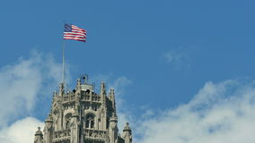 United States of America Flag Waving on the Top of a Skyscraper. USA flag waving on the wind on the top of Chicago Tribune building stock footage