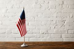 United states of america flagpole on wooden surface against brick wall stock image
