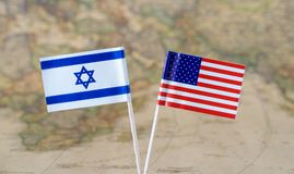 The United States of America and Israel flag pins on a world map background, political relations concept. Paper flag pins of Israel and the United States of stock photos