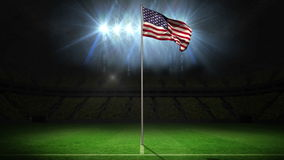 United States of America national flag waving on flagpole. On football pitch with flashes stock footage