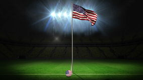 United states of america national flag waving on flagpole. On football pitch with flashes stock video footage