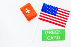United States of America permanent resident cards. Immigration concept. Text green card near passport cover and US flag. Top view on white background royalty free stock image