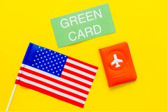 United States of America permanent resident cards. Immigration concept. Text green card near passport cover and US flag. Top view on yellow background royalty free stock photo