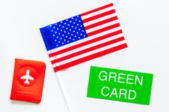 United States of America permanent resident cards. Immigration concept. Text green card near passport cover and US flag. Top view on white background stock photos