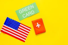 United States of America permanent resident cards. Immigration concept. Text green card near passport cover and US flag. Top view on yellow background royalty free stock photos