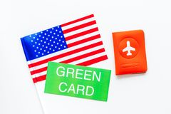United States of America permanent resident cards. Immigration concept. Text green card near passport cover and US flag. Top view on white background stock photography