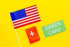 United States of America permanent resident cards. Immigration concept. Text green card near passport cover and US flag. Top view on yellow background stock photography