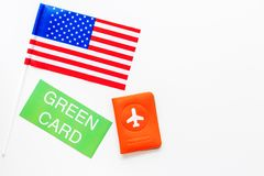 United States of America permanent resident cards. Immigration concept. Text green card near passport cover and US flag. Top view on white background royalty free stock photo