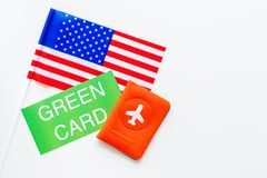 United States of America permanent resident cards. Immigration concept. Text green card near passport cover and US flag. Top view on white background stock image