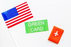 United States of America permanent resident cards. Immigration concept. Text green card near passport cover and US flag. Top view on white background stock images