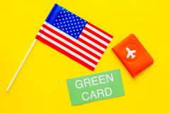 United States of America permanent resident cards. Immigration concept. Text green card near passport cover and US flag. Top view on yellow background royalty free stock photography