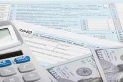 United States of America Tax Form 1040 with calculator and US dollars Stock Photos