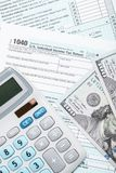 United States of America Tax Form 1040 with calculator and US dollars - close up studio shot. Tax Form 1040 with calculator and US dollars - close up studio shot Royalty Free Stock Images