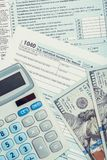 United States of America Tax Form 1040 with calculator and US dollars over it - close up studio shot. Tax Form 1040 with calculator and US dollars over it Royalty Free Stock Photography