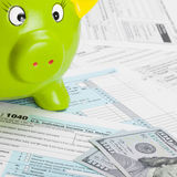 United States of America Tax Form 1040 with green piggy bank - 1 to 1 ratio Stock Image