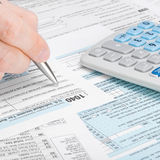 United States of America Tax Form 1040 - man filling out tax form - 1 to 1 ratio Stock Photography